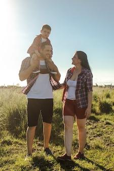 Um pai segurando seu filho nos ombros, com a mãe ao lado deles na campina