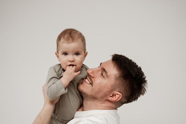 Um pai solteiro abraça seu filho e se alegra com seu rápido crescimento, o bebê olha para a câmera maliciosamente com os dedos na boca