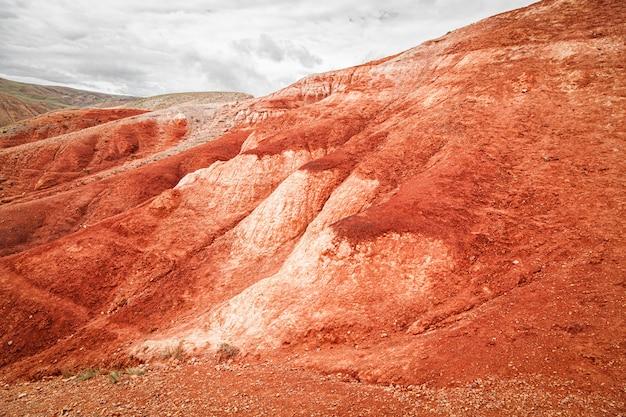 Um panorama deslumbrante de uma cadeia de montanhas de picos, um desfiladeiro com barro vermelho, vista superior.