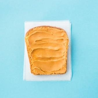 Um pão torrado untado com manteiga de amendoim em um fundo azul
