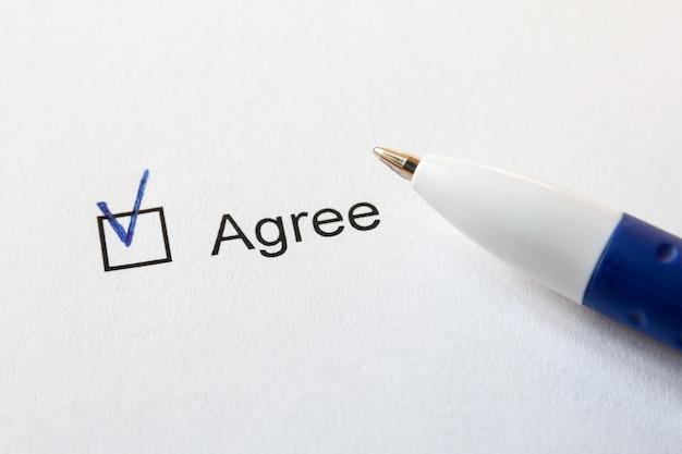 Um papel branco com a opção de concordar e uma caneta azul.