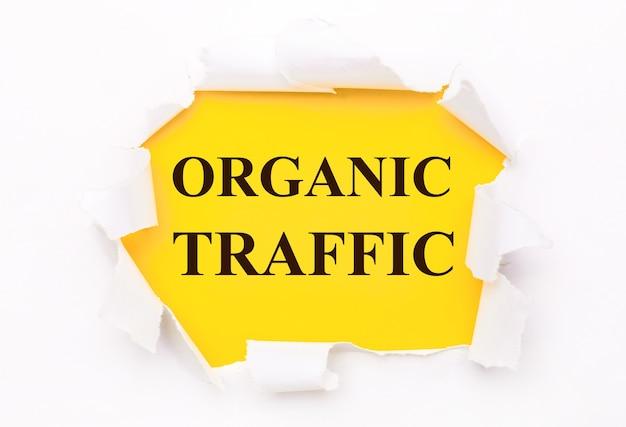 Um papel branco rasgado está sobre um fundo amarelo brilhante com o texto tráfego orgânico
