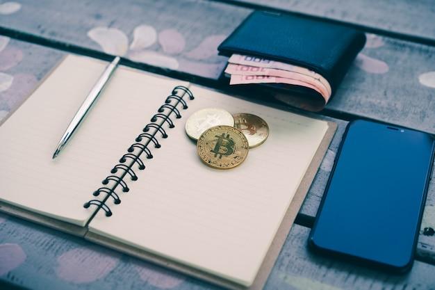 Um papel de caderno com uma caneta, moedas de ouro bitcoin e smartphone na mesa de madeira