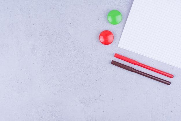 Um papel em branco com canetas coloridas e alfinetes ao redor