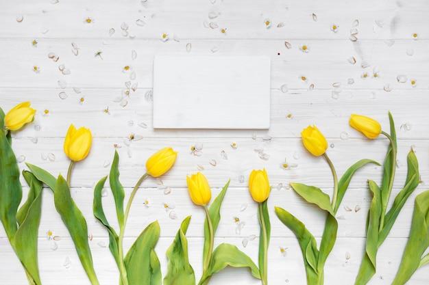 Um papel em branco com tulipas amarelas