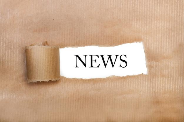 Um papel marrom rasgado com notícias escritas