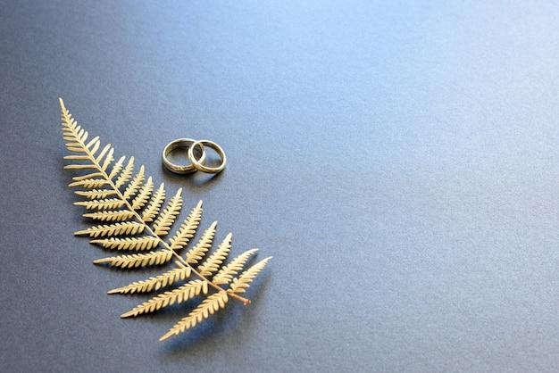 Um par de anéis de alianças de casamento isolado no fundo cinzento.