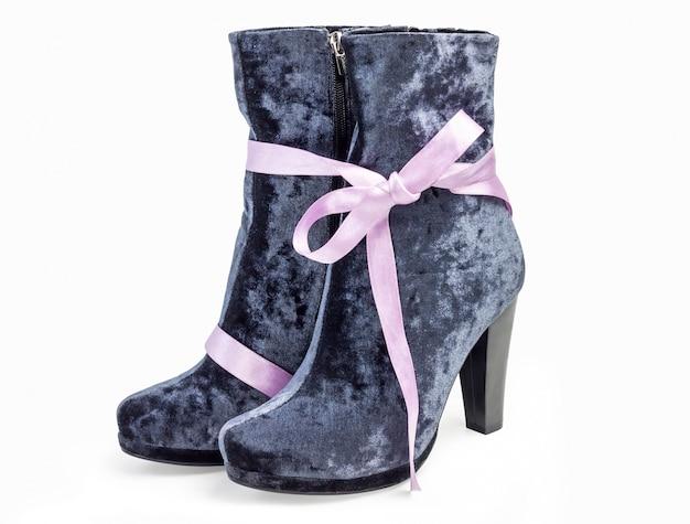 Um par de botas de camurça cinza feminino em pé de saltos no fundo branco