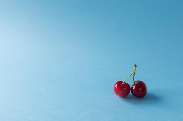 Um par de cerejas sobre um fundo azul claro