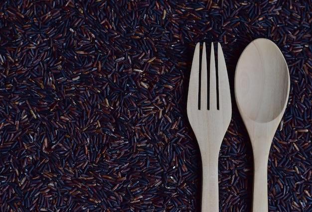 Um par de colher e garfo em riceberry (baga de arroz), que é uma variedade de arroz registrada de