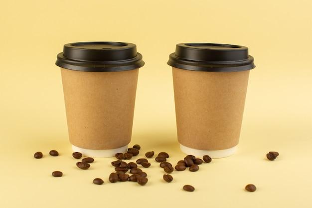 Um par de copos de café de plástico com vista frontal para entrega de café com sementes de café marrom na superfície amarela