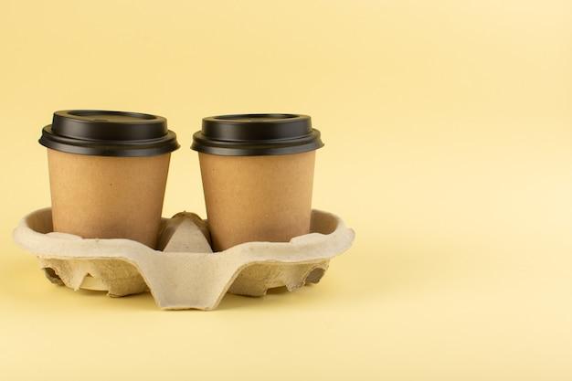 Um par de copos de café de plástico com vista frontal para entrega de café na parede amarela