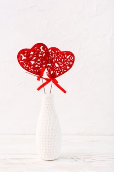 Um par de corações encaracolados vermelhos em um vaso branco decorado por tricô em cima da mesa