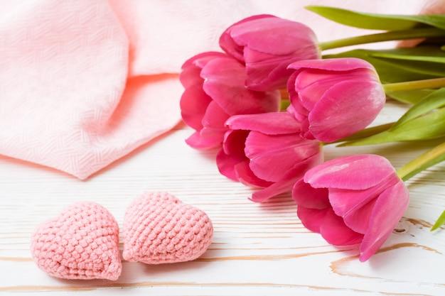 Um par de corações rosa de malha e um buquê de tulipas frescas em uma mesa de madeira