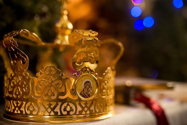 Um par de duas coroas de ouro para casamentos, casamentos no templo da igreja na cerimônia da liturgia divina