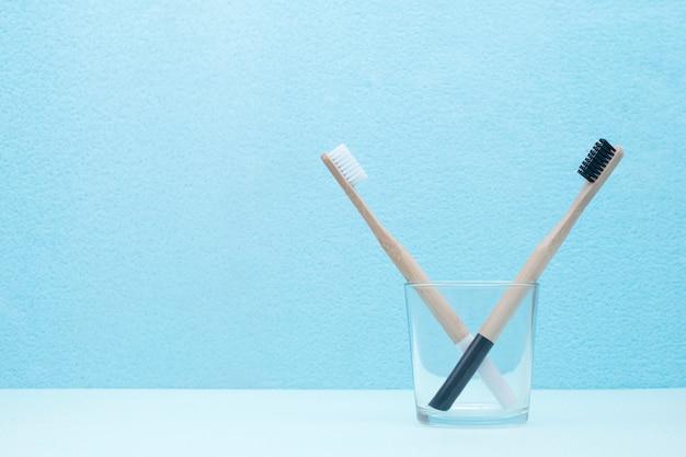 Um par de escovas de dentes de bambu em um vidro transparente sobre um fundo azul com um espaço de cópia.