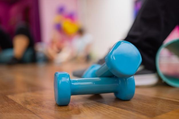 Um par de halteres hexagonais de plástico duro azul deitado no chão emaranhado de borracha de um ginásio ou clube de saúde.