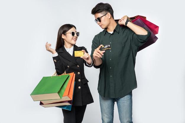 Um par de homens e mulheres usando óculos e carregando muitos sacos de papel para fazer compras
