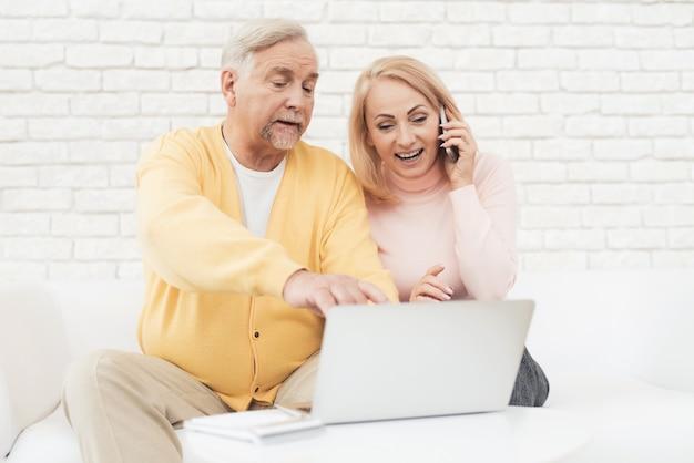 Um par de idosos está sentado na frente de um computador portátil.