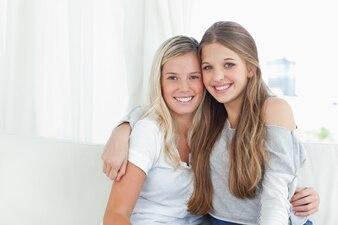 Um par de irmãs se abraçam enquanto olham para a câmera