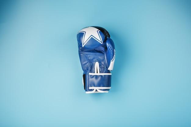 Um par de luvas de boxe de couro em um fundo azul, espaço livre.
