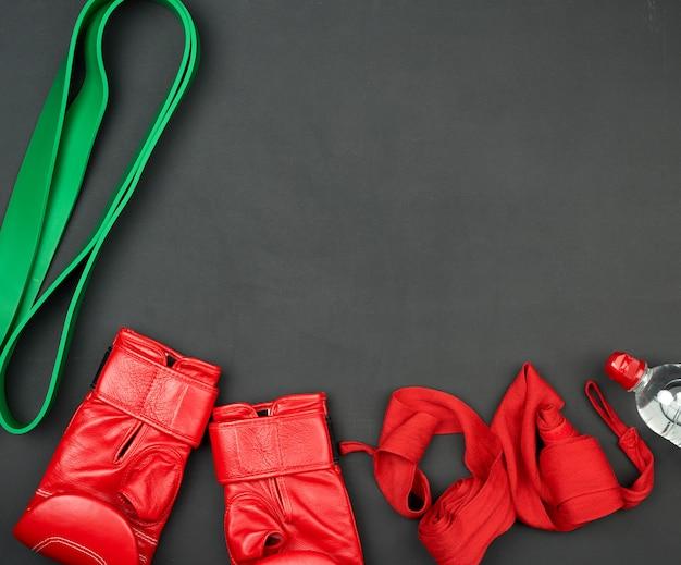 Um par de luvas de boxe de couro vermelho, um curativo têxtil e uma garrafa de água