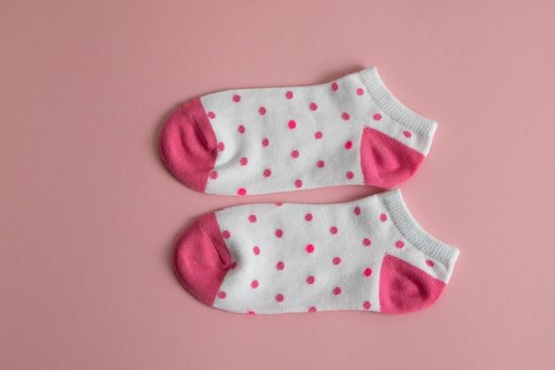 Um par de meias brancas para crianças com meias e saltos cor-de-rosa, com pontos cor-de-rosa,