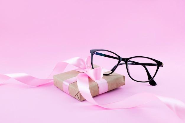 Um par de óculos pretos na superfície rosa
