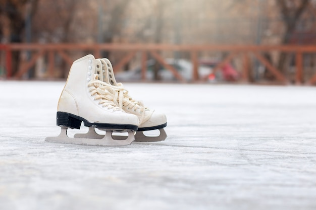 Um par de patins brancos estão de pé em uma pista de gelo aberta. esporte de inverno