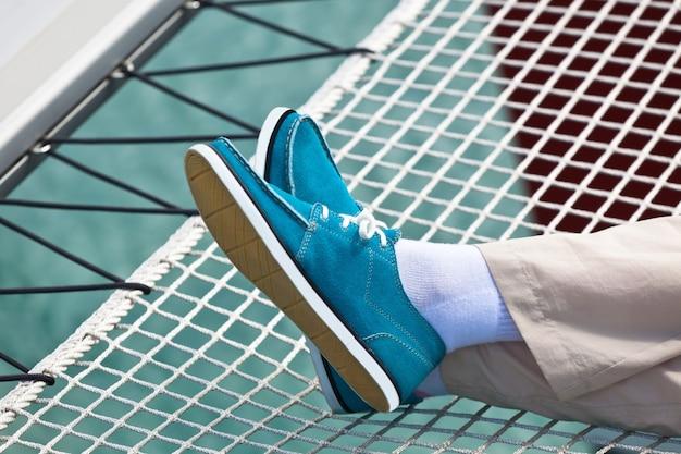 Um par de pernas humanas em calças e topsiders azuis brilhantes no fundo da rede do iate. iatismo