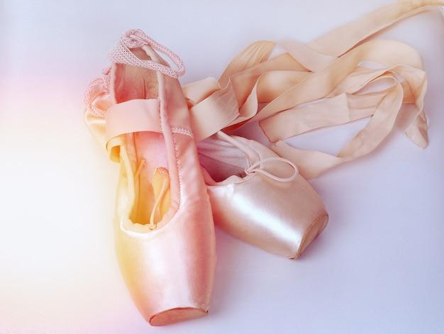 Um par de sapatilhas de ballet rosa. pointes em um branco.