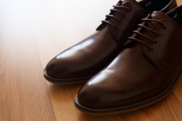 Um par de sapatos de couro marrom em um assoalho de madeira