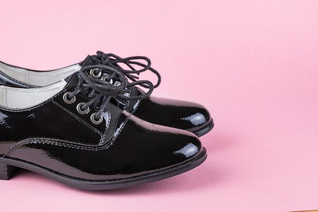 Um par de sapatos femininos da moda negra em um fundo rosa.