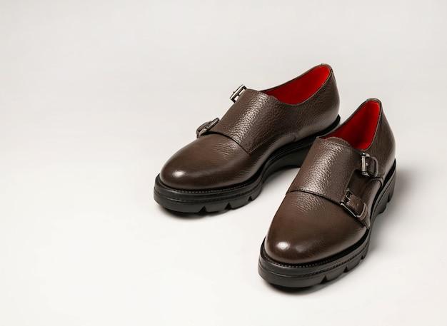 Um par de sapatos femininos de couro marrom com fundo branco, close-up