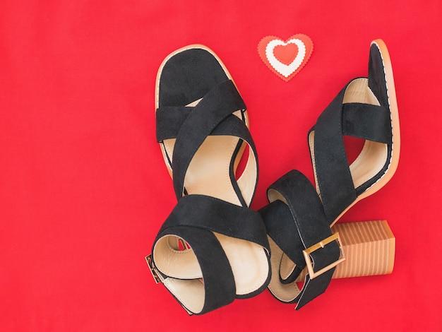 Um par de sapatos femininos lindos e uma figura de coração em um pano vermelho. o conceito de terminar um relacionamento amoroso. postura plana.
