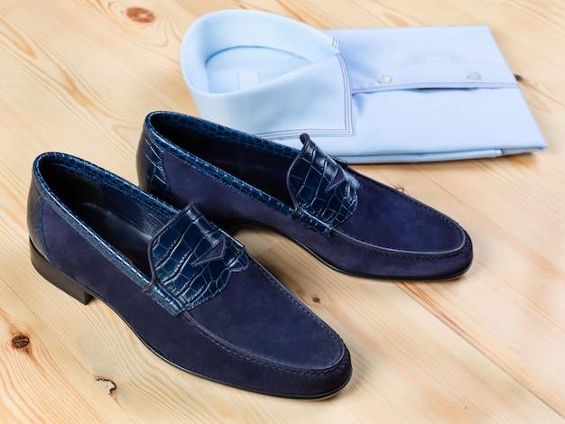 Um par de sapatos masculinos de camurça azul e couro de crocodilo e uma camisa com fundo de madeira