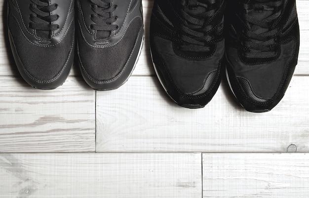 Um par de sapatos masculinos e femininos no chão de madeira