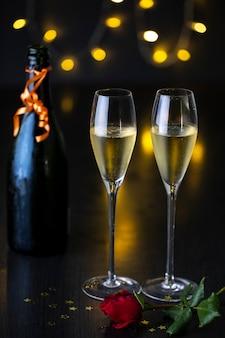 Um par de taças de champanhe com uma rosa em uma mesa e uma garrafa de champanhe.