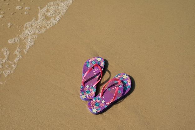 Um par de vibrantes sandálias roxas flip-flops na praia de areia com onda swash, praia de copacabana, brasil