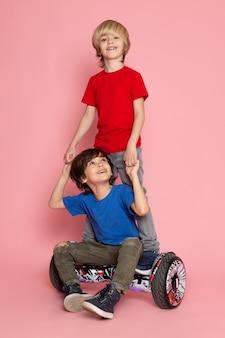 Um par de vista frontal de meninos em camisetas coloridas andando de segway no espaço rosa