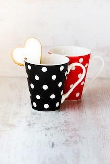 Um par de xícaras de café preto e vermelho com bolinhas.