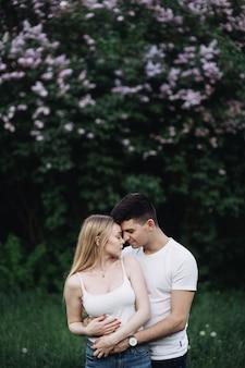 Um, par jovem, apaixonadas, abraçando, e, desfrutando, a, momento, frente, um, florescendo, bush