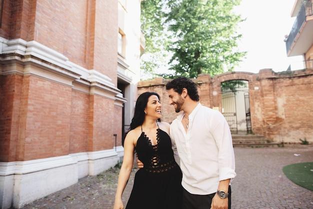 Um par novo do amor que aprecia uma caminhada no pátio da cidade velha.