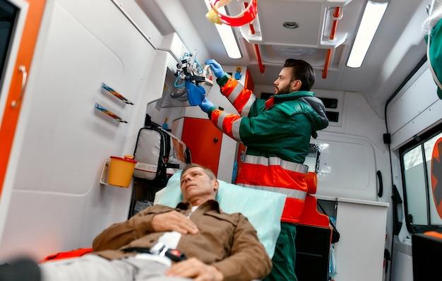 Um paramédico uniformizado procura uma máscara de oxigênio para ajudar um paciente idoso deitado em uma maca em uma ambulância moderna.