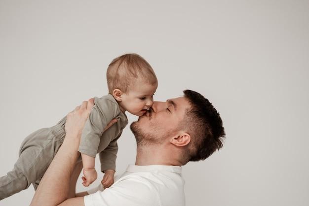 Um parente de uma criança pequena está feliz com seu primeiro encontro, beija o bebê na bochecha, segurando bem alto em seus braços, uma foto tirada em uma sala iluminada sobre um fundo branco