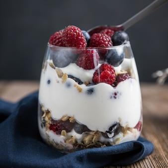 Um parfait de granola com frutas vermelhas e iogurte em um fundo preto