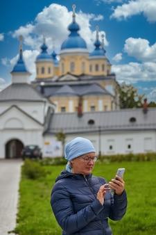 Um paroquiano crente com um telefone no contexto da igreja ortodoxa. mulher com smartphone no templo