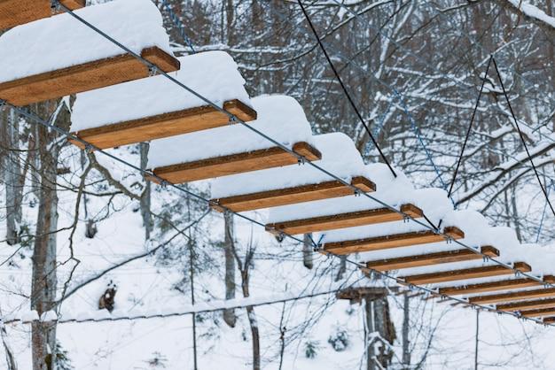 Um parque de corda extrema coberto de neve branca está localizado em árvores em ruínas na floresta deserta dos cárpatos no inverno