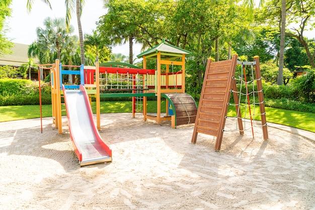 Um parque infantil, uma barra deslizante localizada na areia.