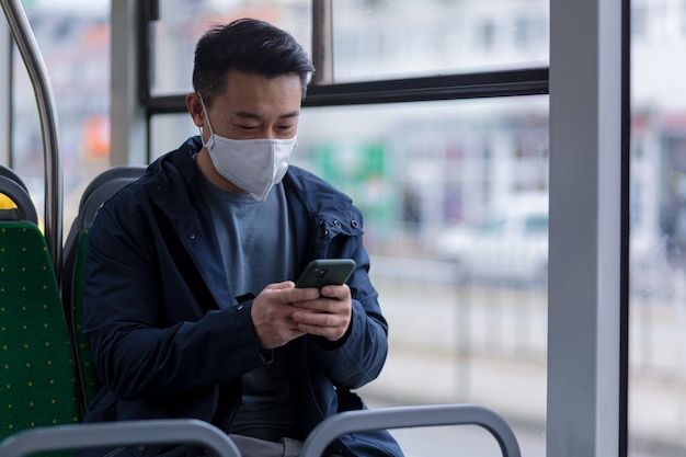 Um passageiro asiático com uma máscara médica protetora no rosto ansiosamente escreve e lê notícias de um telefone celular, um homem viaja pela cidade em um ônibus de transporte público